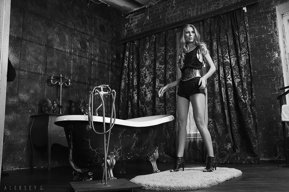 Black & white photo of a girl in a bathroom | glamour, model, girl, black & white, blonde, bath, black, rug, long legs, curtain