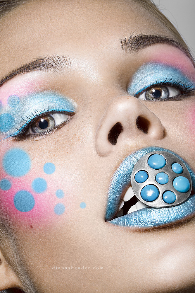 Girl covered with a blue make-up holds ring in her mouth | make-up, ring, mouth