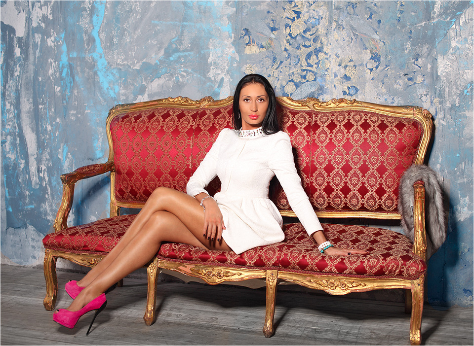 Ugly model sitting on the couch | ugly model, couch, high-heeled shoes, short dress