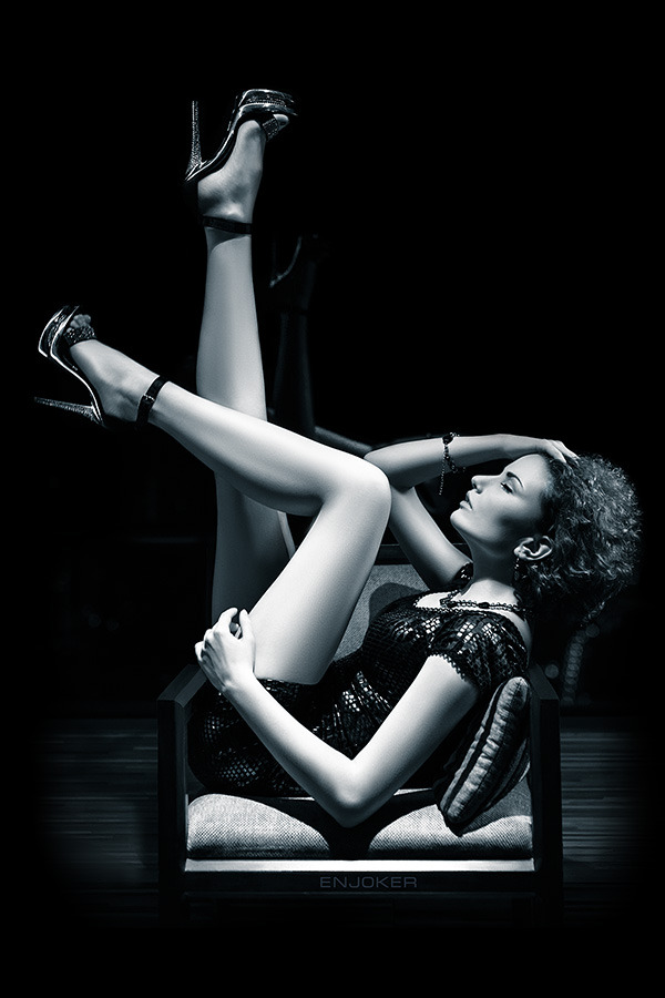 Twisted girl in chair   black & white, short skirt, high-heeled shoes, curly hair, chair, room